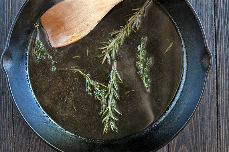 A wooden spoon stirs sprigs of fresh rosemary and thyme in a dark colored liquid, in a cast iron pan.