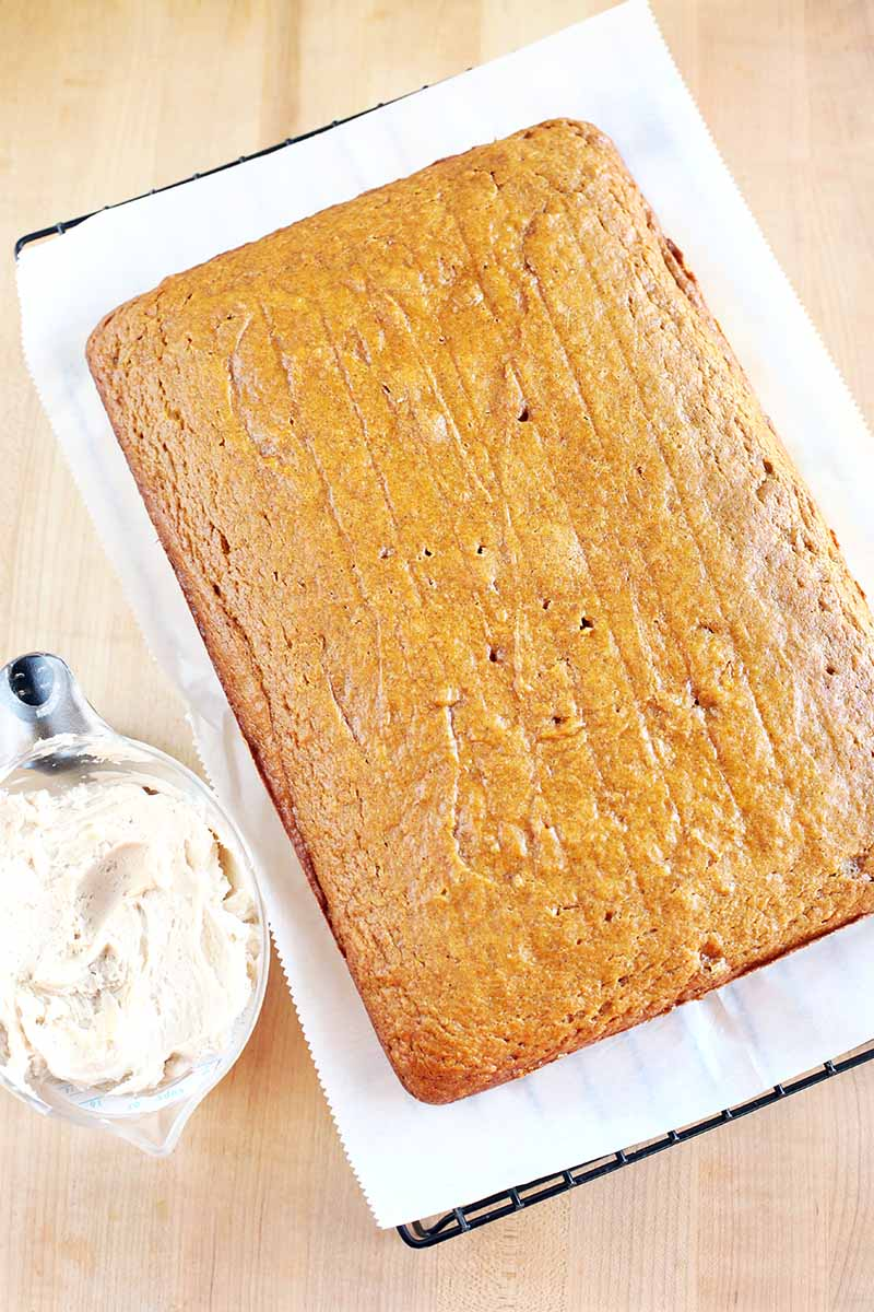 A rectangular pumpkin sheet cake on a piece of white parchment paper on top of a black metal cooling rack, beside a glass measuring cup of vanilla spiced buttercream frosting, on a beige wood countertop.