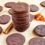 Chocolate cookies are scattered on a beige wooden surface, with a spoonful of cayenne pepper, cinnamon sticks, and a tall stack of cookies in the middle.