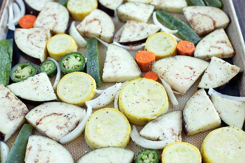 Sliced and chopped vegetables are sprinkled with salt and pepper, and arranged on a baking sheet.