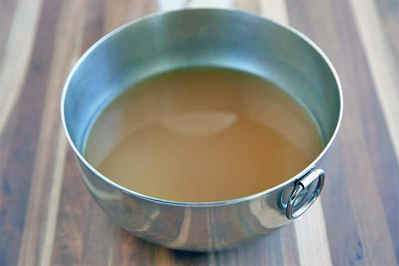 A stainless steel bowl is filled with a light brown liquid, on a striped brown and tan wood surface.