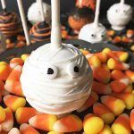 Horizontal image of assorted Halloween-themed desserts on sticks with candy corn.