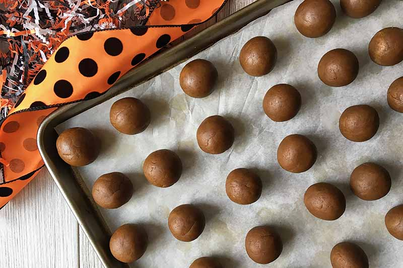 Horizontal image of dessert balls on a baking sheet lined with parchment paper next to orange and black ribbons.