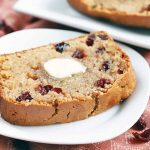 A slice of homemade cranberry quick bread with a pat of melting butter on top is on a white plate, with a large white rectangular ceramic serving platter of more of the baked good in the background, on a surface topped with a pink tablecloth, with scattered pieces of dried fruit.