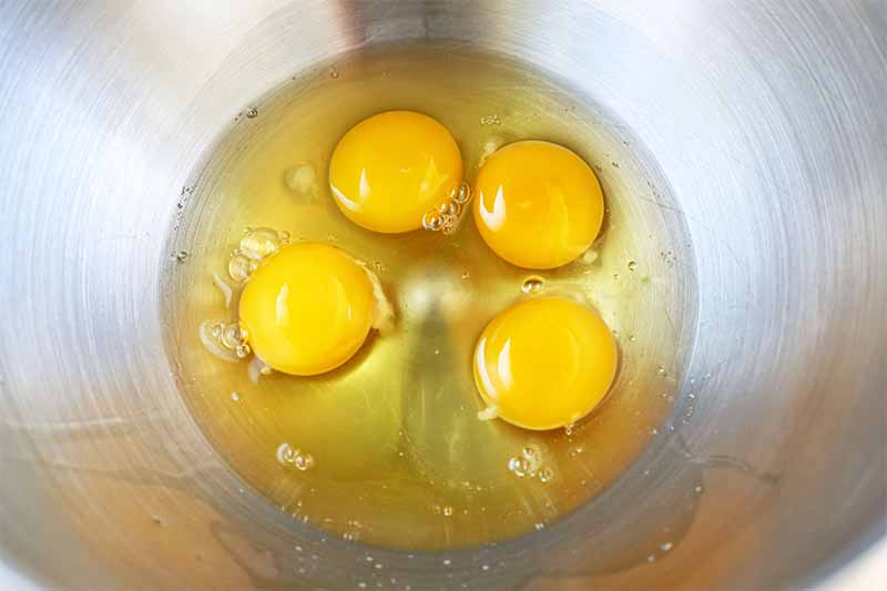 Four eggs cracked into a stainless steel mixing bowl.