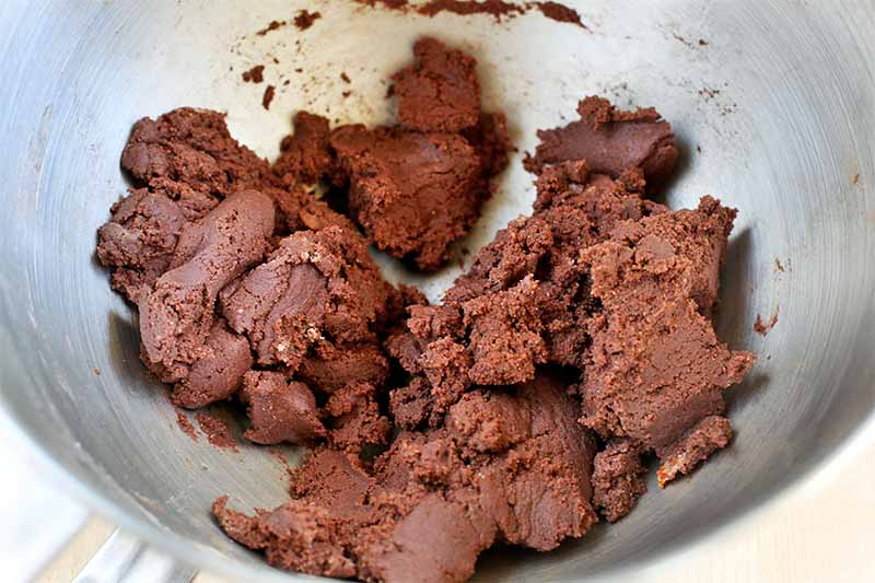 Clumps of a thick chocolate cookie dough are at the bottom of a stainless steel mixing bowl.