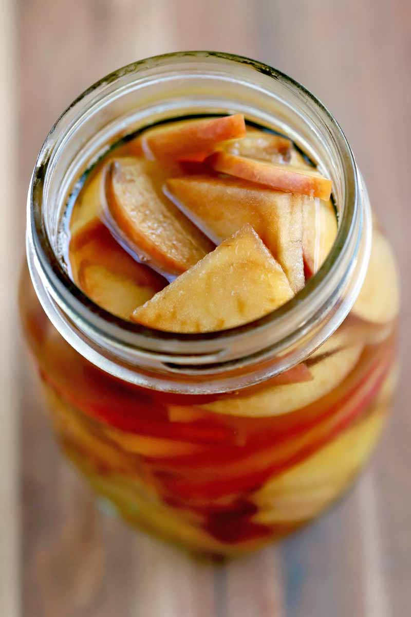 A jar of sliced apples soaked in brandy, on a wood surface.