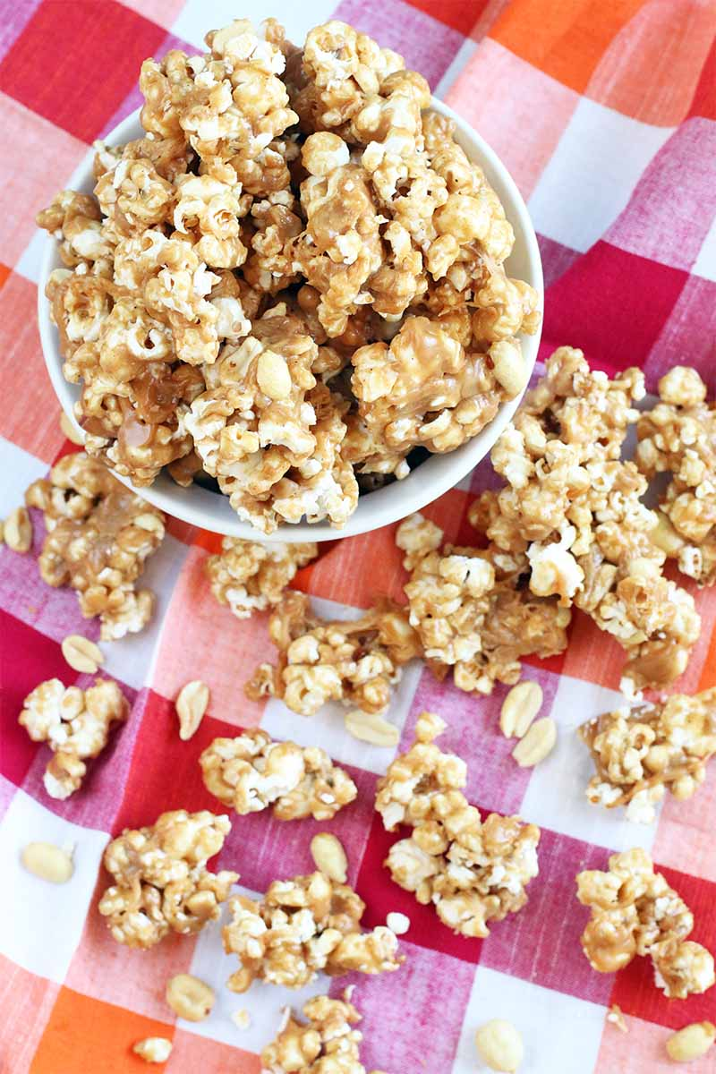 Top-down shot of a white dish of peanut butter caramel popcorn, with more scattered around it on a red, white, and orange checkered tablecloth.