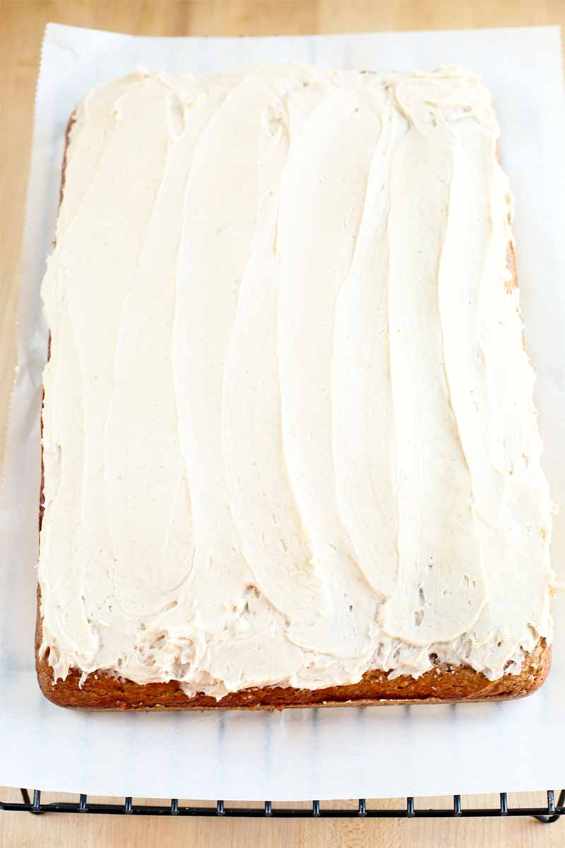 Top-down shot of a pumpkin slab cake topped with vanilla buttercream frosting, on a metal cooling rack topped with a sheet of white parchment paper, on a beige surface.