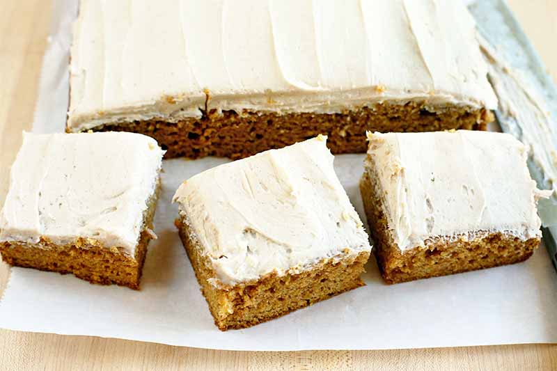 Three slices of pumpkin cake with vanilla frosting in front of the rest of the slab, on a white piece of parchment on a beige countertop.