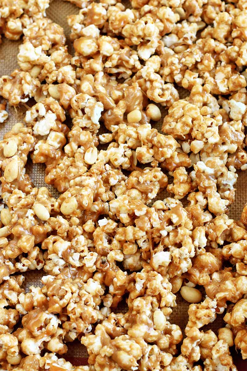 Closeup of homemade peanut butter caramel popcorn on a Silpat silicone pan liner, filling the frame.