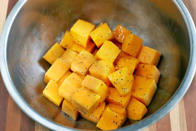 A stainless steel bowl of peeled and cubed butternut squash, sprinkled with salt and pepper.