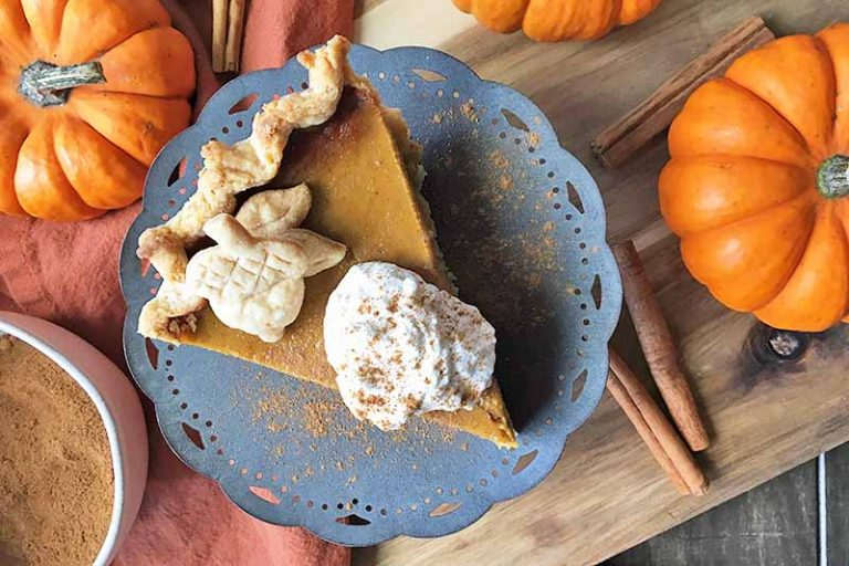 Horizontal image of a slice of pie with a bowl of spices, cinnamon sticks, and mini squash.