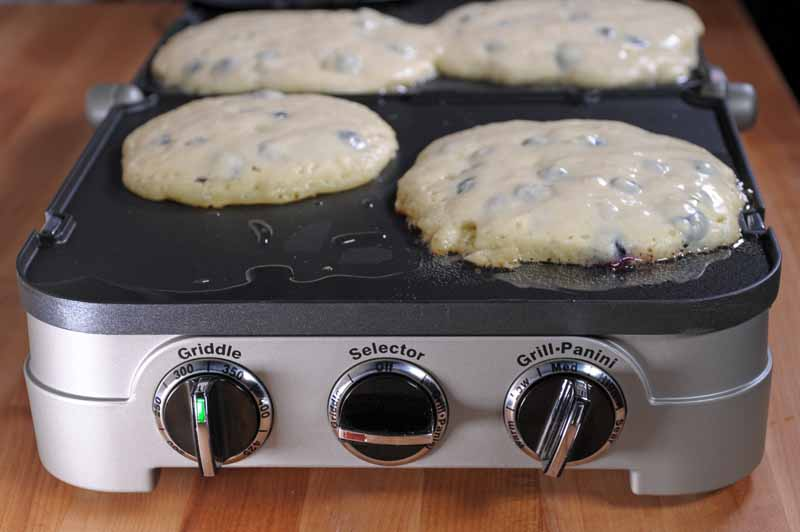 A close up of the Cuisinart GR-4N 5-in-1 Griddler showing the front dials and blueberry pancakes cooking on top.