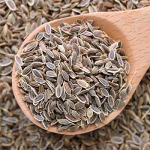 Top down view of dill seeds in a wooden spoon