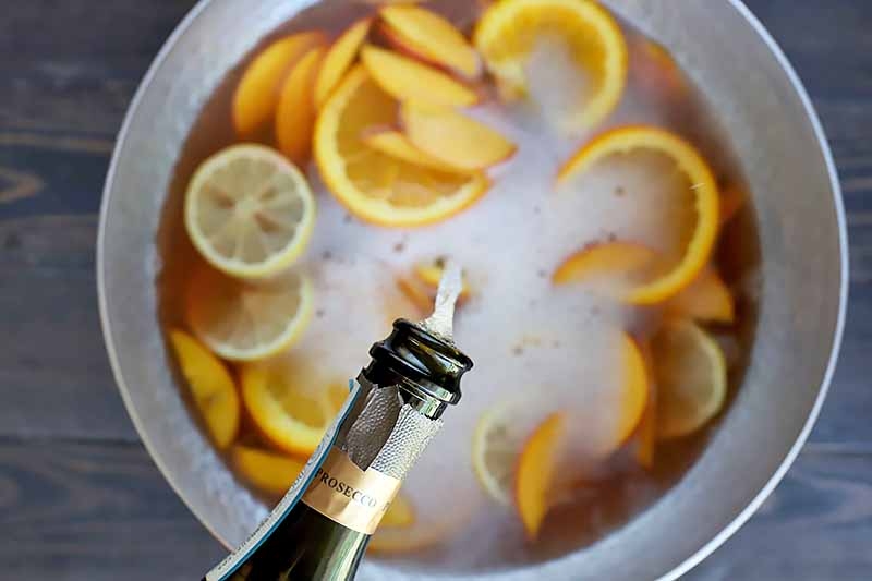 Horizontal image of pouring prosecco into a bowl with sliced oranges, lemons, and peaches.
