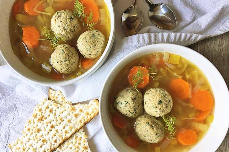 Horizontal image of two bowls of broth with matzo dumplings on white towels with crackers and spoons.