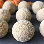 Horizontal image of rows of white chocolate truffles with pumpkins.
