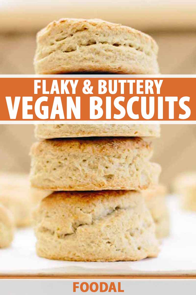 A stack of four homemade vegan biscuits on a piece of white parchment, with more in shallow focus against a beige tile backdrop, printed with orange and white text.