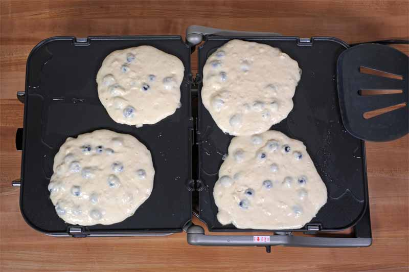 Top view of four blueberry pancakes cooking on the Cuisinart GR-4N 5-in-1 Griddler