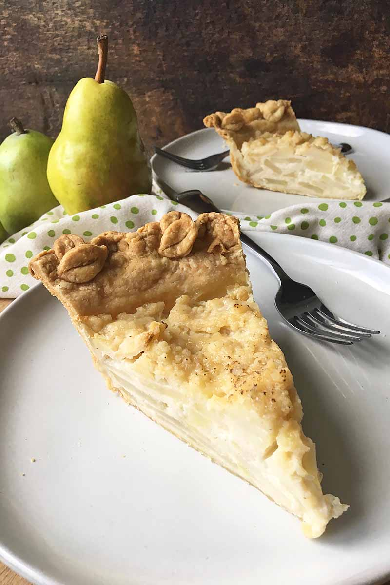 Vertical image of two slices of pie on white plates with metal forks with whole pears.