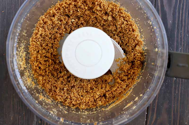Horizontal image of a crumbled graham cracker mixture in a food processor.