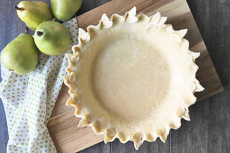 Horizontal image of an unbaked pie shell on a wooden board next to fruit and a green polka-dot napkin.