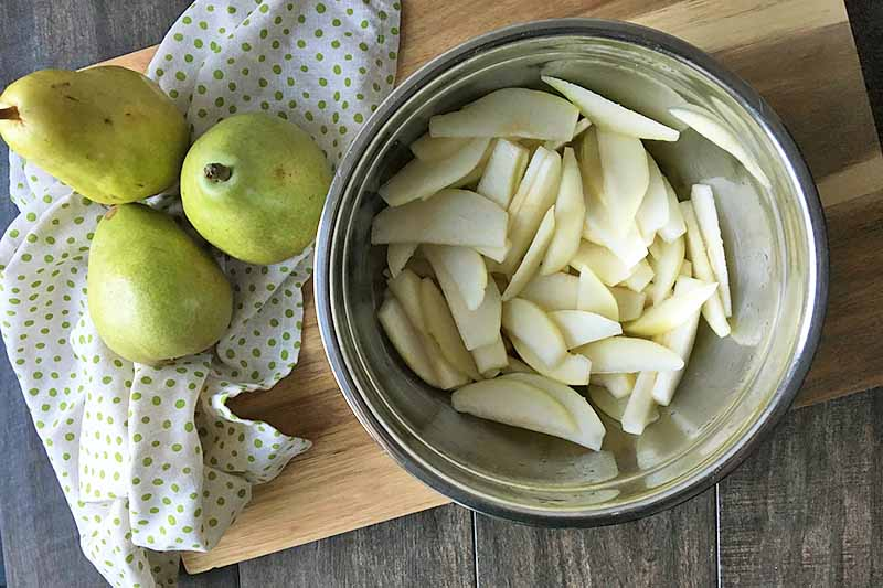 Horizontal image of a metal bowl with slices of pear on a wooden board next to pears and a green polka-dot napkin.