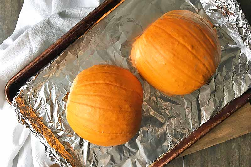 Horizontal image of two orange squash halves cut side down on a tray lined with aluminum foil.