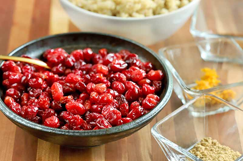 A gray bowl of roasted cranberries with a gold spoon, next to three square clear glass dishes of citrus zest and spices, with a white bowl of cooked quinoa in the background, on a striped wood surface.