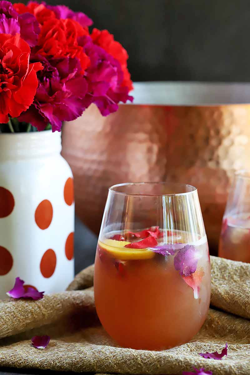 Vertical image of one beverage in a glass next to a copper bowl and a polka-dot vase with flowers.