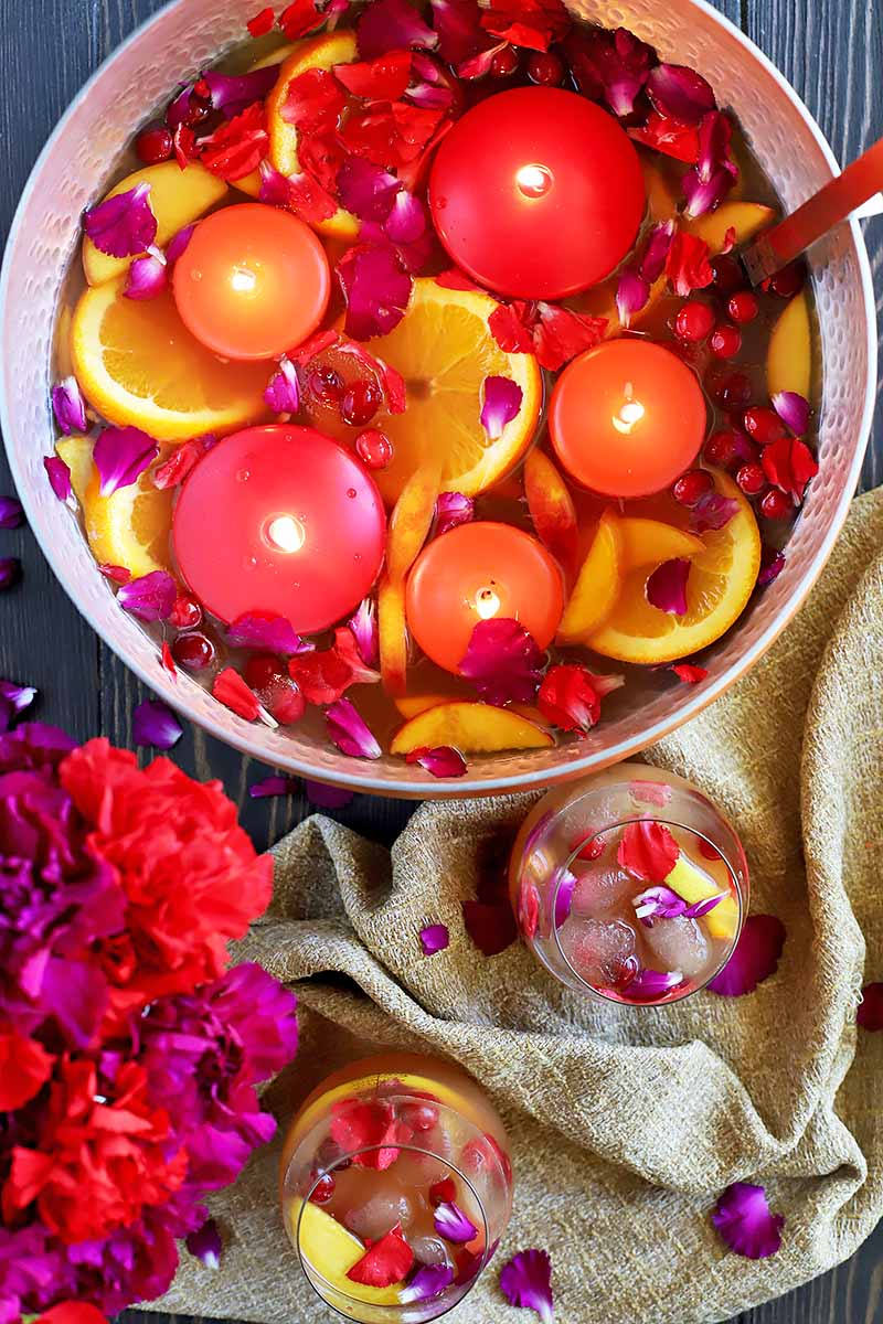 Vertical top-down image of a large bowl with punch, a cocktail glass, and flowers.