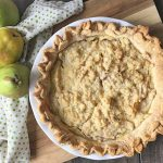 Horizontal image of a whole pie topped with streusel on a wooden cutting board next to three pears.