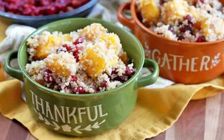 Two Thanksgiving-themed orange and green double-handled ceramic crocks of quinoa with winter squash and cranberries, on a yellow cloth on top of a wood surface, with a blue bowl of roasted berries on a beige cloth in the background.