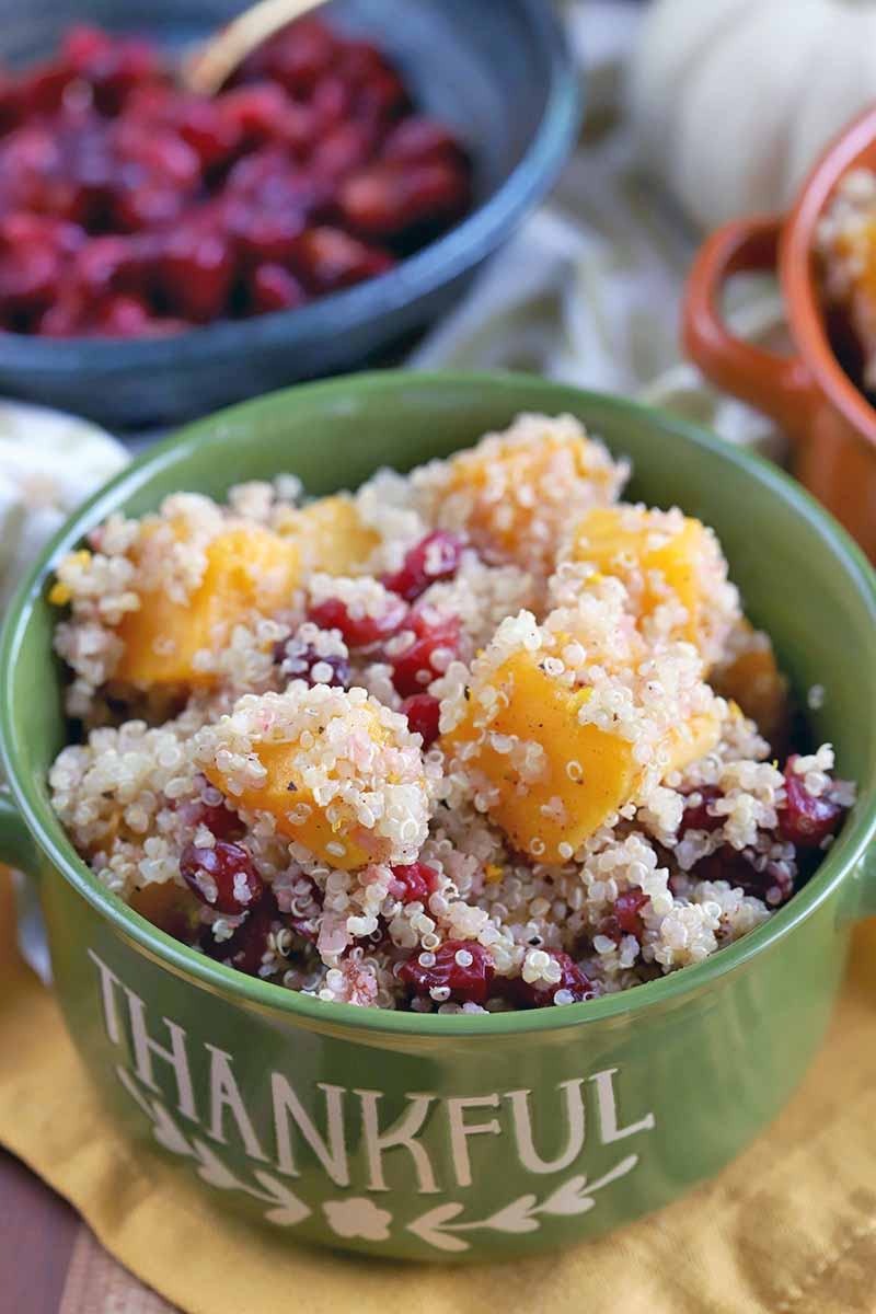 Vertical overhead oblique shot of a green ceramic crock filled with a quinoa, squash and cranberry side dish, with another matching dish in orange int he background, beside a blue bowl of roasted berries, on a yellow cloth.