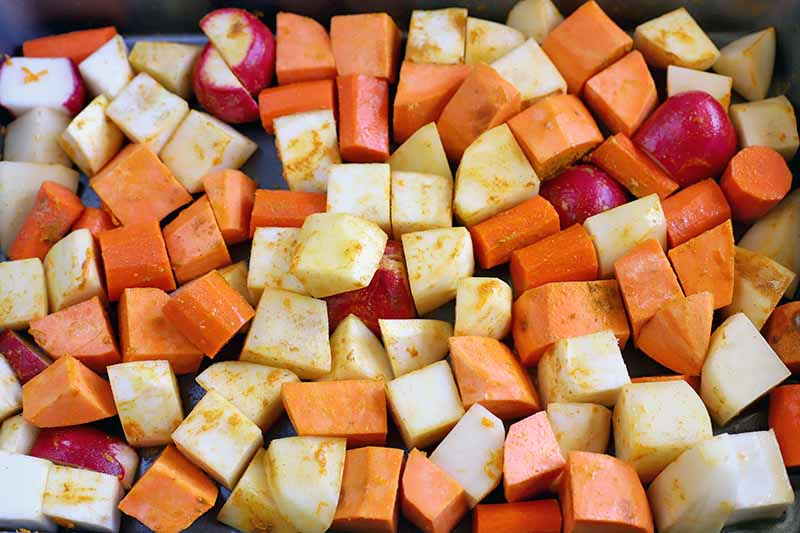 Peeled and chopped root vegetables sprinkled with spices, in a metal baking pan.