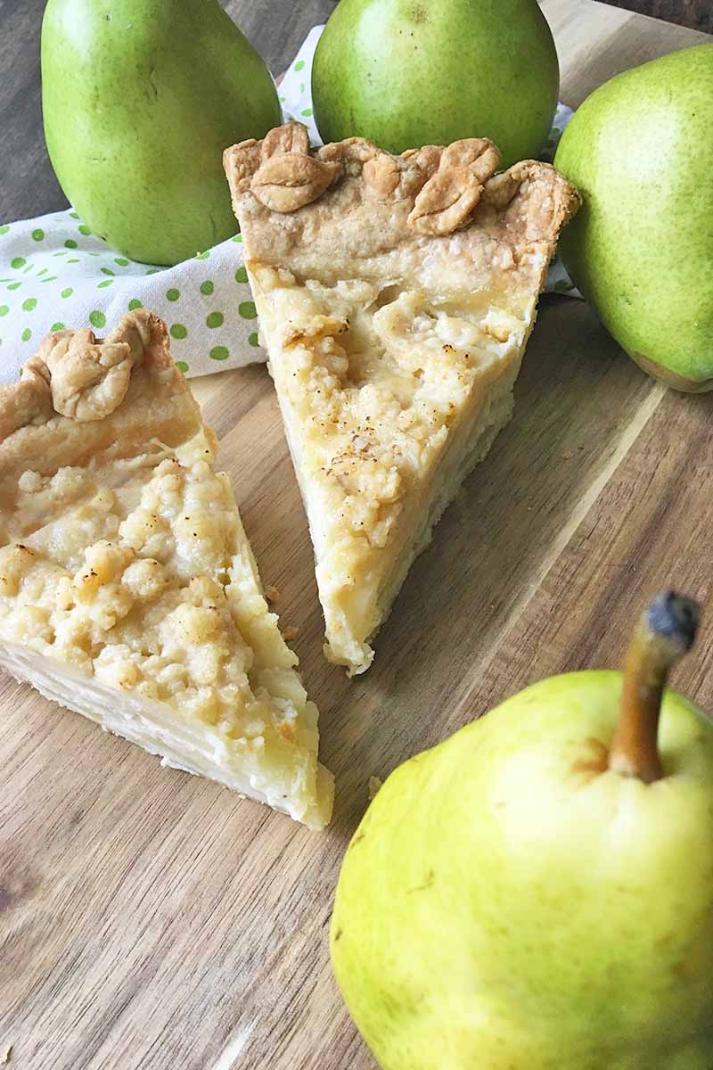 Vertical image of two slices of pie on a wooden cutting board next to pieces of fruit.