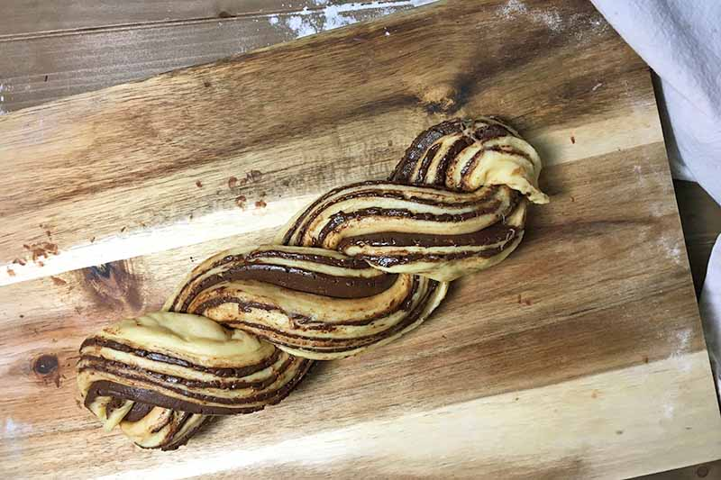 Horizontal image of an unbaked braided bread with chocolate lines.