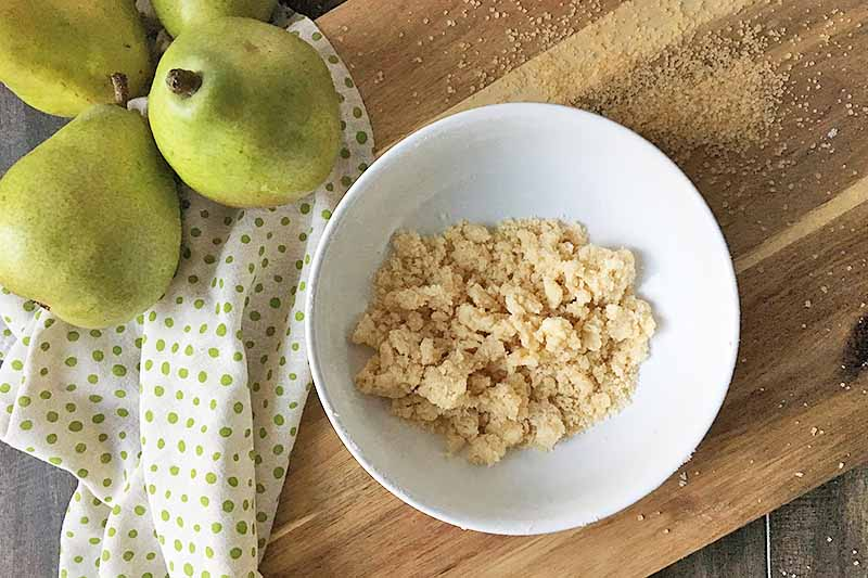 Horizontal image of a bowl of unbaked streusel topping in a white bowl next to fruit and a napkin.