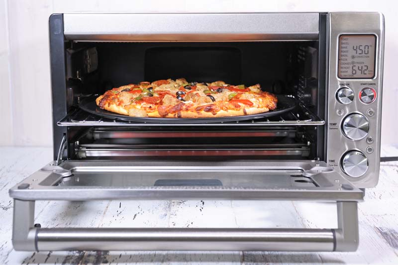 A front view of a Breville Smart Convection Toaster Oven baking a pizza.