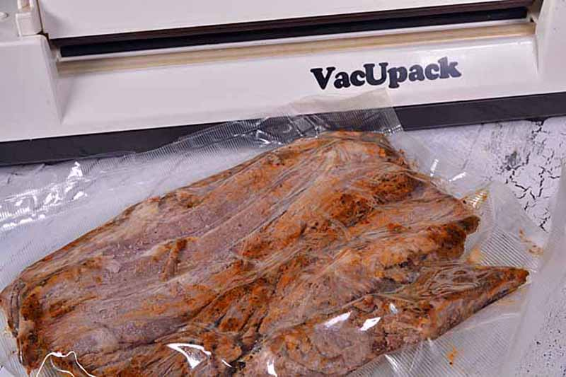 Close up of a vacuum sealer being used to seal brisket slices in a plastic bag.