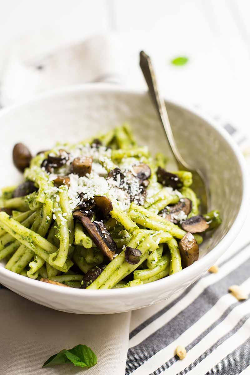 Vertical image of a white bowl with pasta, mushrooms, and a green sauce.