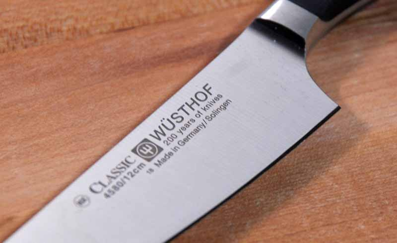 Close up of a laser engraved Wusthof logo on the Classic 4.5 in. Asian Utility Kitchen Surfer Knife. On a medium toned wooden background.
