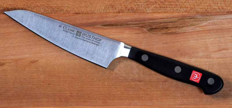 The Wusthof Classic 4.5 in. Asian Utility Kitchen Surfer Knife on a maple butcher block surface.