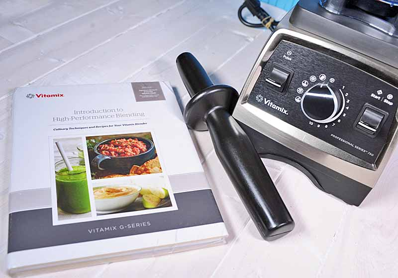 The Getting Started book, recipe book, and the tamper that comes with the Vitamix 750 Professional Series Blender on a white painted wooden surface.