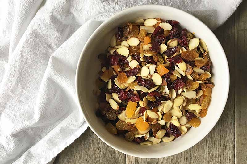 Horizontal image of a white bowl with assorted dried fruits and nuts on top of a white towel.