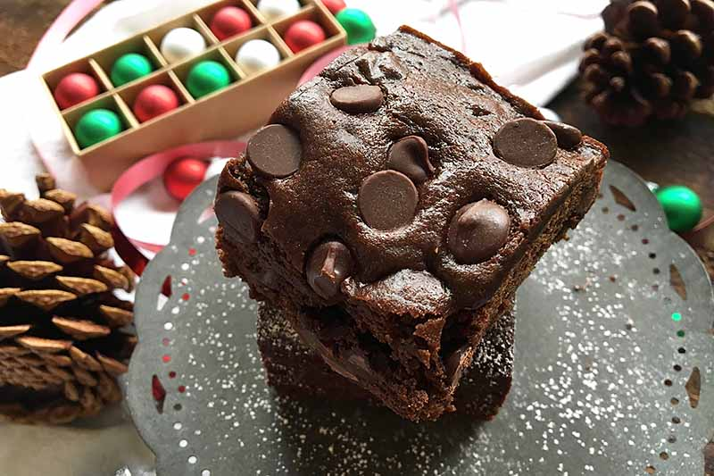 Horizontal image of cake squares with chips on a tray in front of mini Christmas tree decorations.