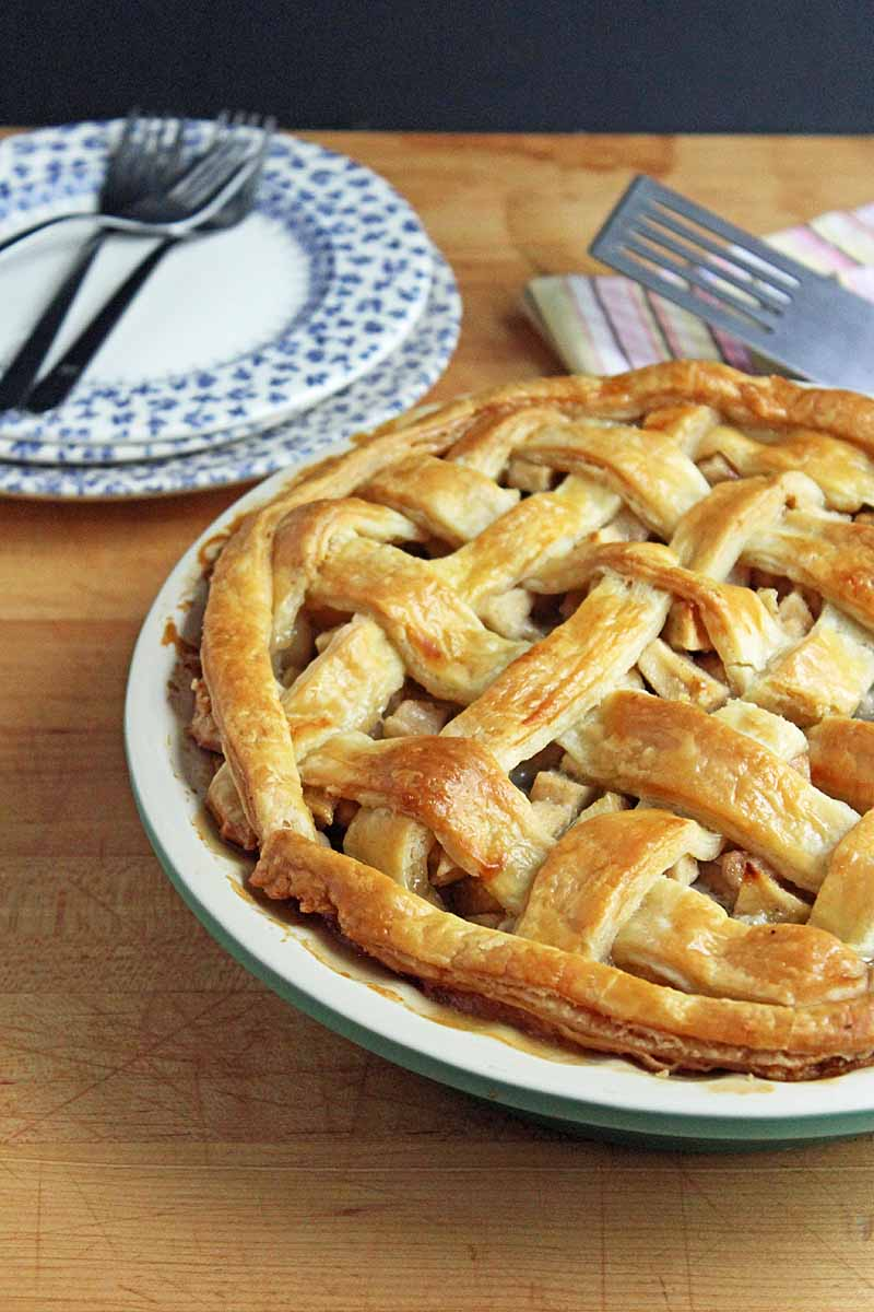 Oblique view of a half a apple pear pie sitting on a maple wood surface. Two white and blue patterned saucers and forks are in the background.