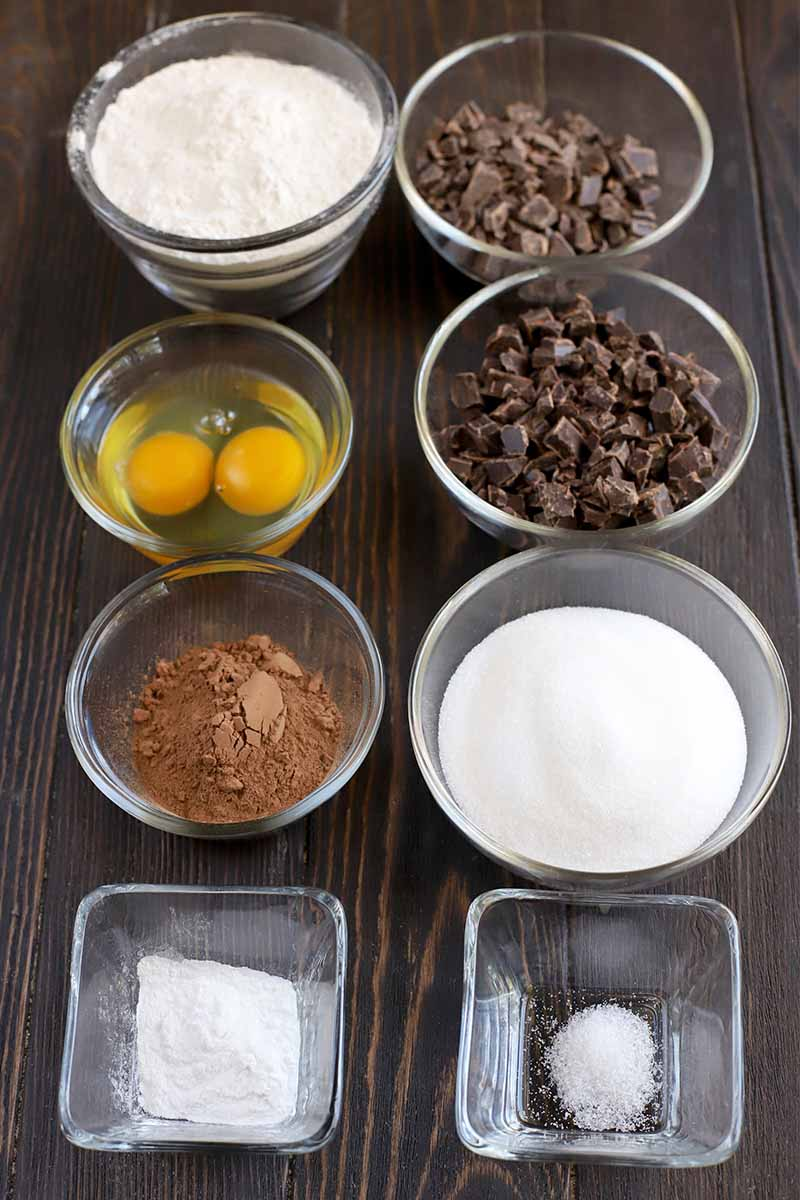 Vertical oblique shot of small round and square glass dishes of flour, chocolate chunks, cracked eggs, cocoa powder, sugar, salt, and baking powder.