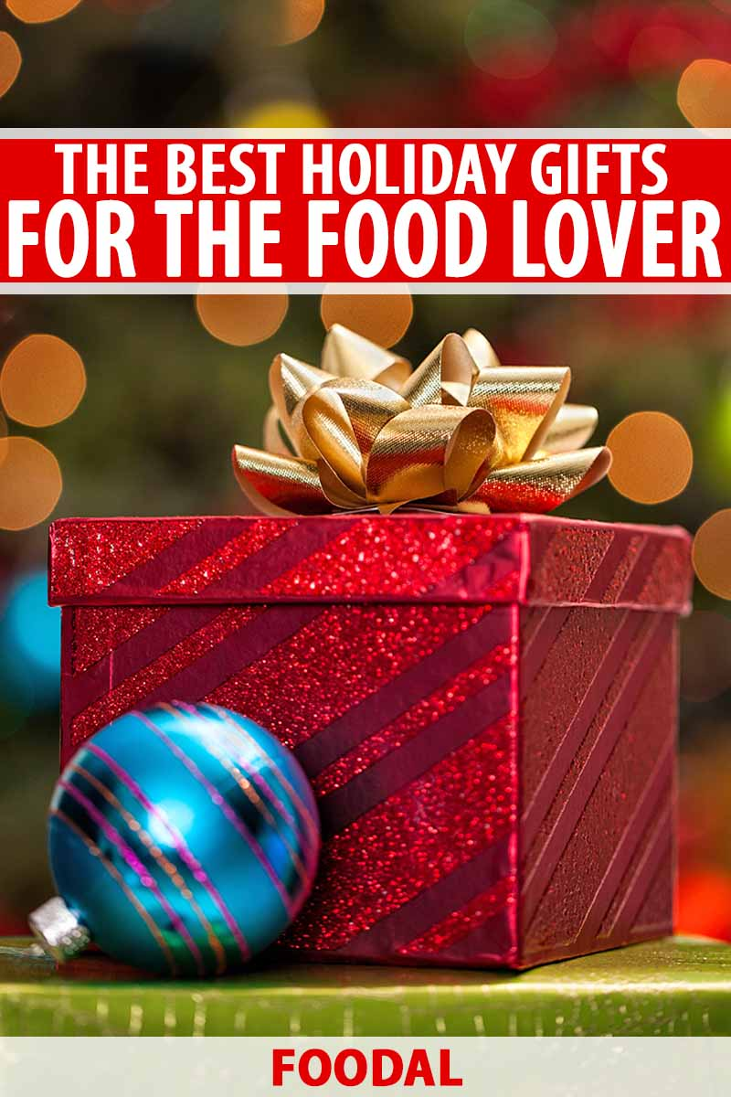 Vertical image of a red striped metallic gift box topped with a gold ribbon with a blue tree ornament in the foreground and a lit evergreen tree in soft focus in the background with bokeh, printed with red and white text.
